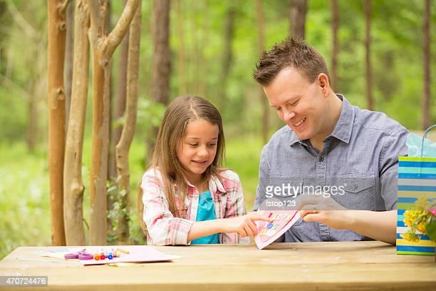 Menina mostra Pai dia cartão feitos à mão do pai. Ao ar livre. Criança, pais.
