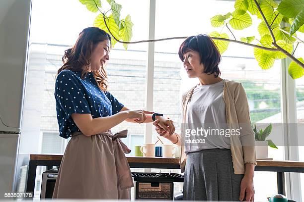 Daughter shows senior mother smartwatch in the kitchen