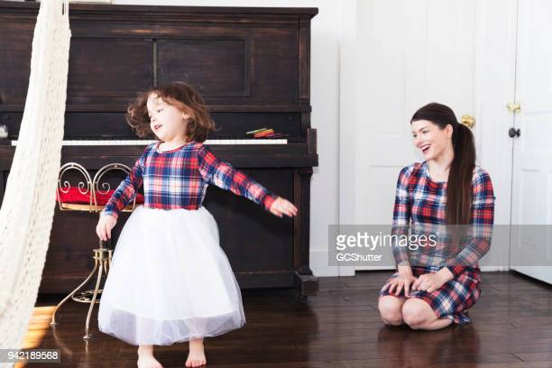 Daughter singing and dancing for her happy mother