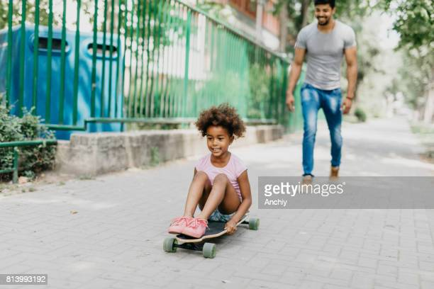 Daughter sits on the longboard and gets pushed by her father.