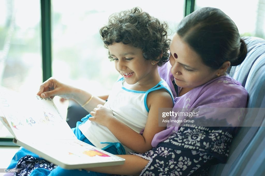 Daughter sitting on mothers lap, reading a book : Stock Photo