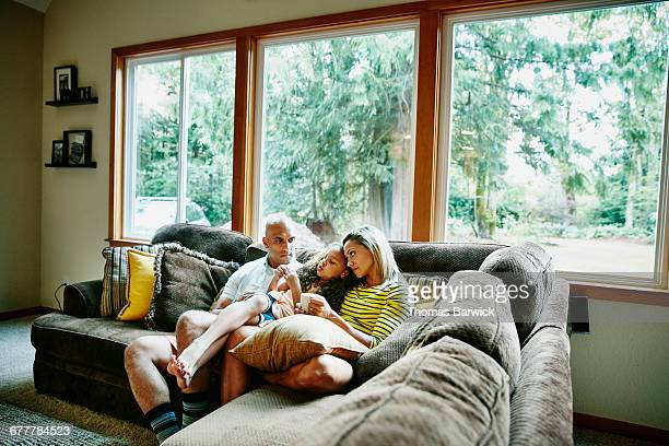 Daughter sitting on parents lap in living room