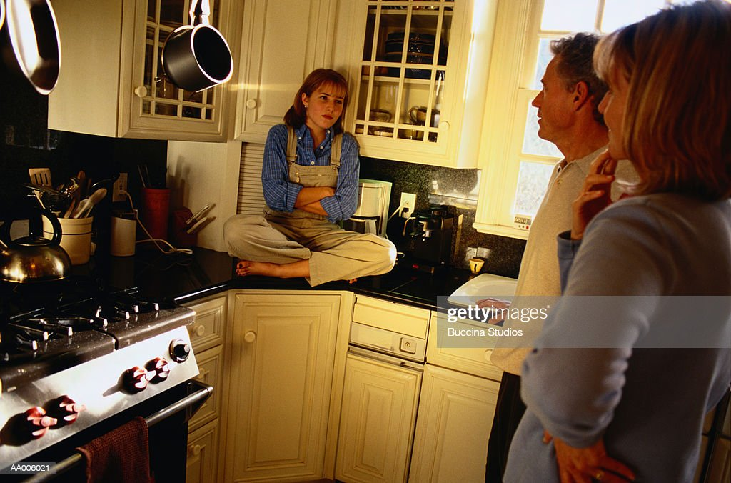 Daughter Sitting on the Counter in the Kitchen : Stock Photo