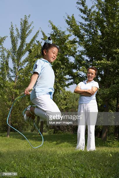 a daughter skips rope enthusiastically as her mother looks on. - skipping along stock pictures, royalty-free photos & images