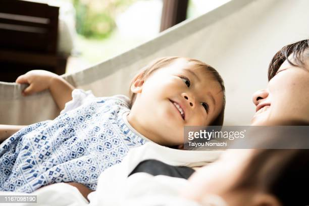 daughter smiling at mother during nap time - 昼寝 ストックフォトと画像