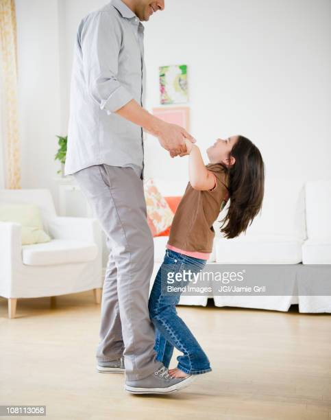 daughter standing on father's feet and dancing - arab feet photos et images de collection