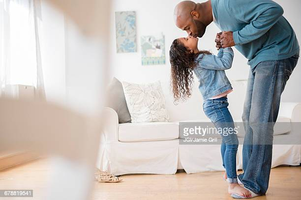 Daughter standing on feet of father and dancing