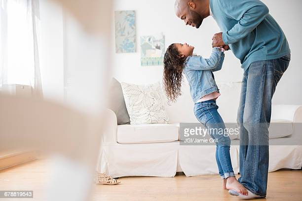 daughter standing on feet of father and dancing - african american family home stock photos and pictures