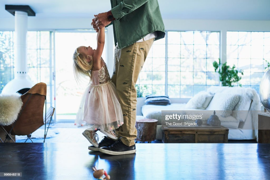 Daughter standing on feet of father dancing : Stock Photo