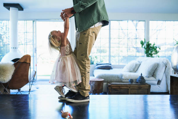 daughter standing on feet of father dancing - authentic relationship stock pictures, royalty-free photos & images