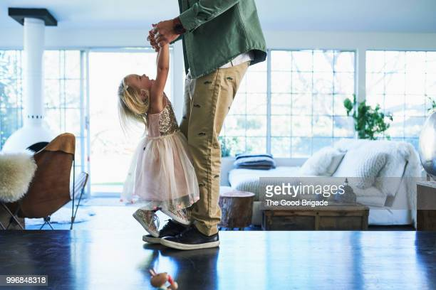 daughter standing on feet of father dancing - giochi per bambini foto e immagini stock