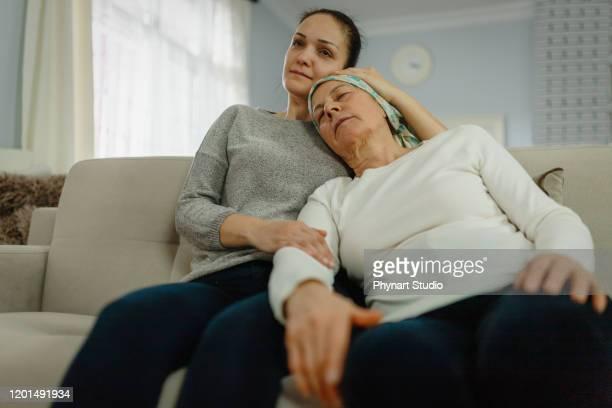 daughter  supporting and hugging her mom with cancer - cancer illness imagens e fotografias de stock