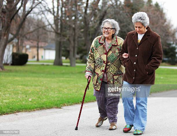 daughter supporting mother using cane - walking cane stock photos and pictures