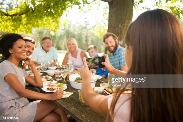 daughter taking a group photo at a family get-together - family reunion stock pictures, royalty-free photos & images