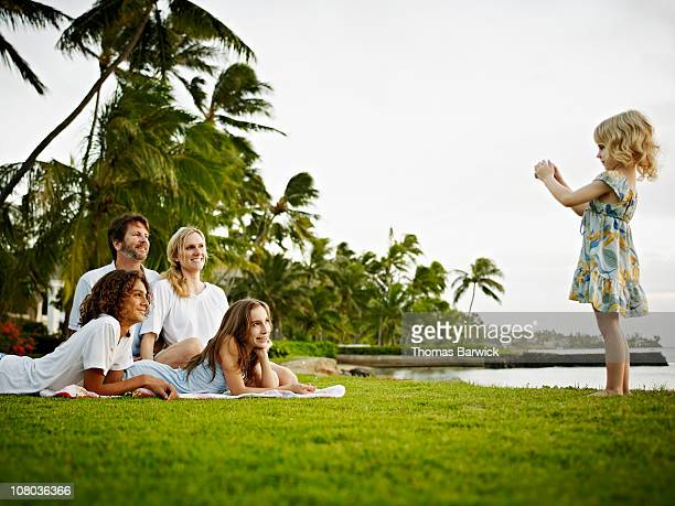 Daughter taking digital photo of family on grass