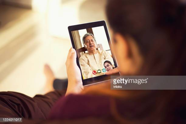daughter talking on video call with her father using digital tablet - looking at camera stock pictures, royalty-free photos & images