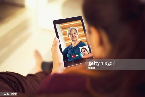 tochter im videoanruf mit ihrer mutter mit digitalem tablet - mother daughter webcam stock-fotos und bilder