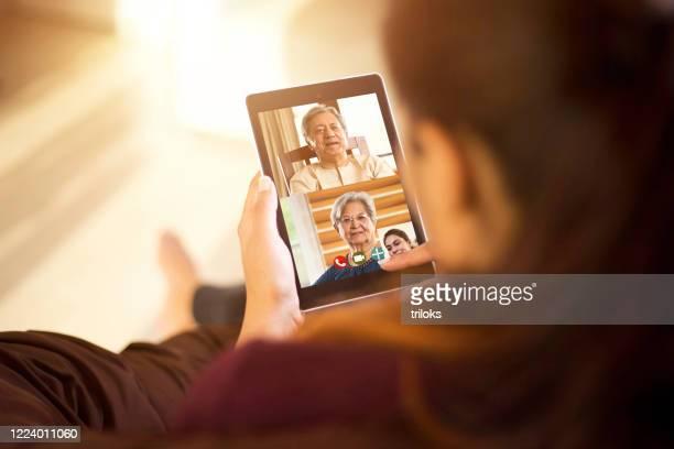 tochter im videoanruf mit ihren eltern mit digitalem tablet - mother daughter webcam stock-fotos und bilder