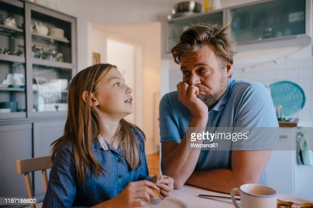daughter talking to father in kitchen at home - father stock pictures, royalty-free photos & images