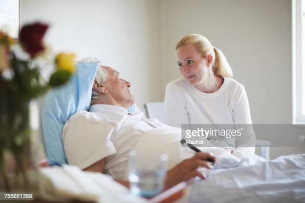daughter talking to senior man reclining on hospital bed - visit stock pictures, royalty-free photos & images