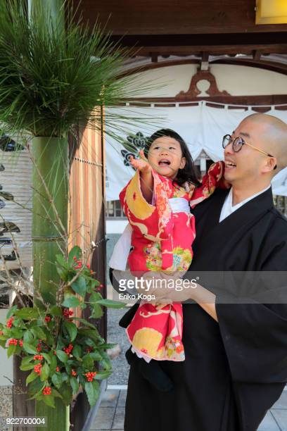 Daughter touching pine of New year's decoration called kadomatsu with father