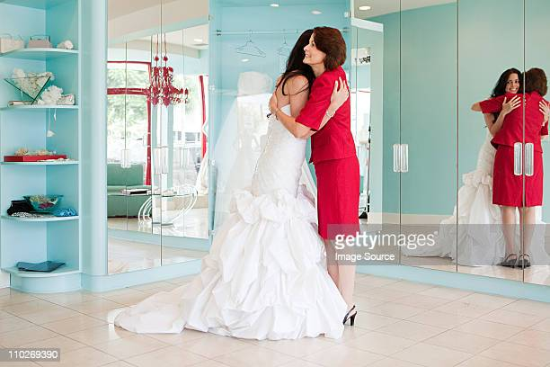 Daughter trying on wedding dress, embracing mother