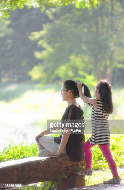 Daughter Tying Hair Of Mother