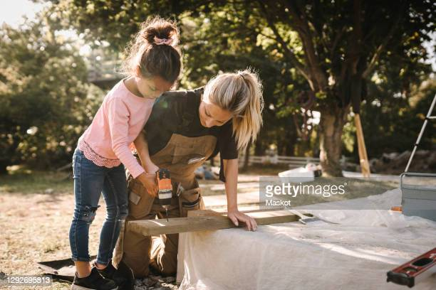 daughter using drill machine on wooden plank by mother in backyard - renovation stock pictures, royalty-free photos & images