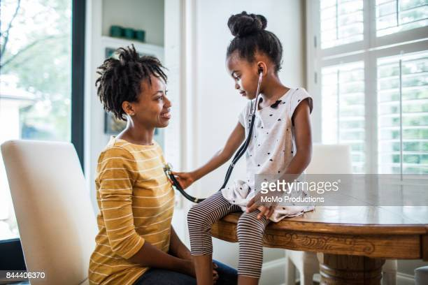 daughter using stethoscope on mother - stethoscope stock pictures, royalty-free photos & images