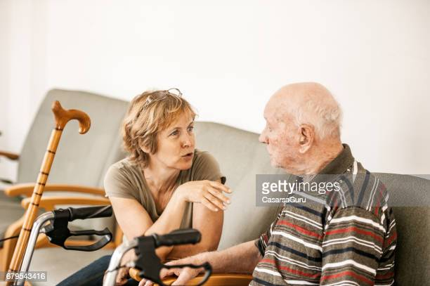 daughter visiting father in the retirement community - residential care stock photos and pictures
