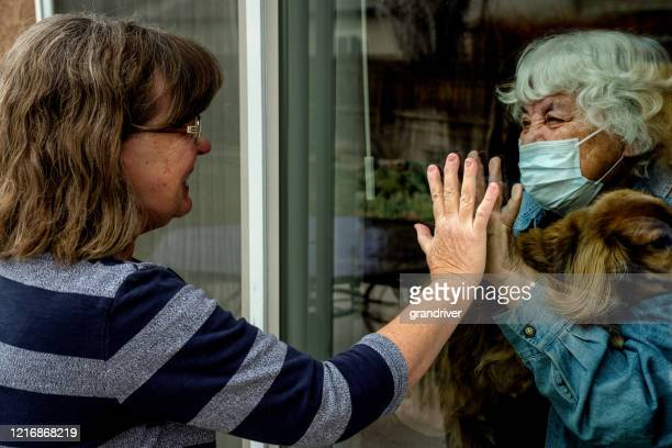 a daughter visiting her quarantined mother preventing contracting corona virus through the window - social distancing stock pictures, royalty-free photos & images
