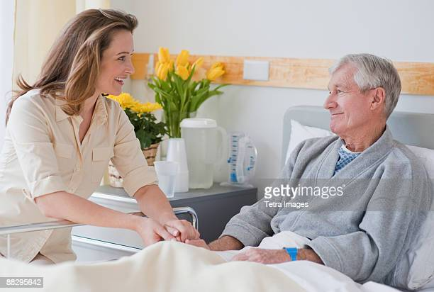 Daughter visiting senior father in hospital