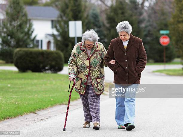 daughter walking with mother using cane - walking cane stock photos and pictures