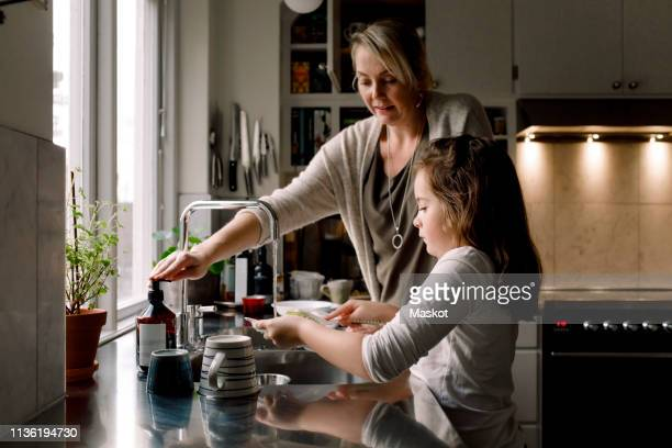 daughter washing dishes while standing by mother in kitchen at home - rutina fotografías e imágenes de stock