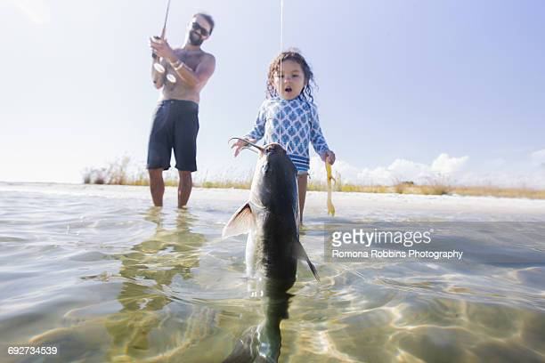 Daughter watching father catch fish in sea, Fort Walton Beach, Florida, USA