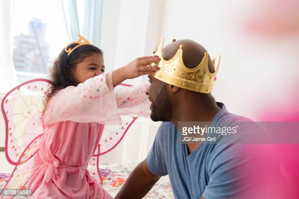 Daughter wearing costume placing crown on father