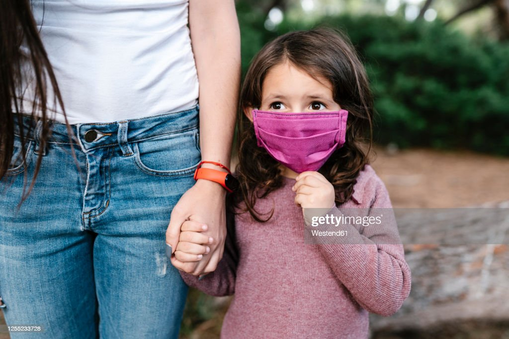 Daughter wearing protective mask and holding hand of her mother : Stock Photo