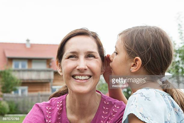 Daughter whispering in mothers ear