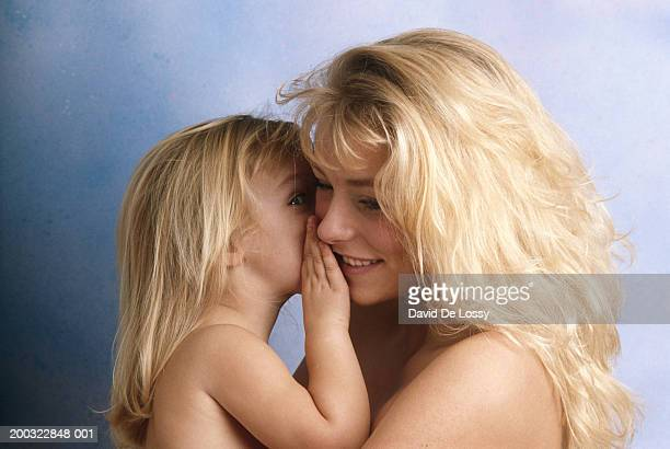 Daughter (2-3) whispering into mother's ear