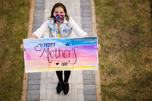 Daughter wishing Happy Mother's Day holding sign 1221506882
