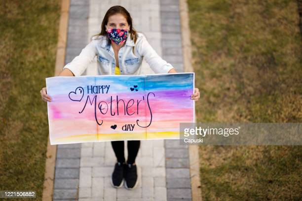 daughter wishing happy mother's day holding sign - mother's day stock pictures, royalty-free photos & images