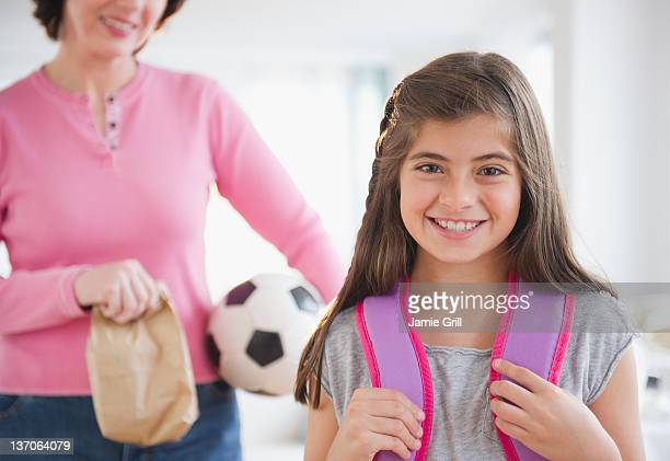 Daughter with backpack, soccer mom in background