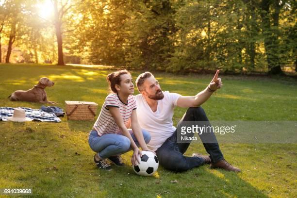 Tochter mit Blick auf Vater entfernt auf Wiese gegen Bäume zeigen ball