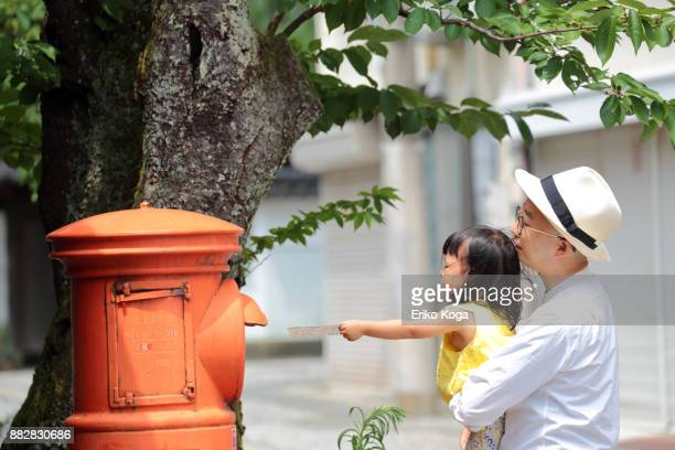 Daughter with father posting in mailbox