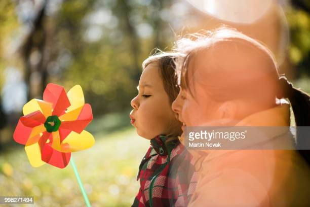 daughter with mother play with pinwheel - paper windmill stock photos and pictures