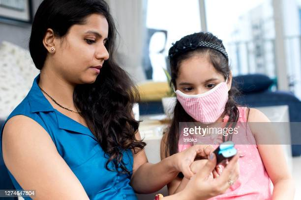 daughter with mother using finger pulse oximeter - pulse oximeter stock pictures, royalty-free photos & images