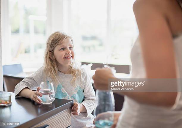 Daughter with water glass and mother in kitchen in kitchen