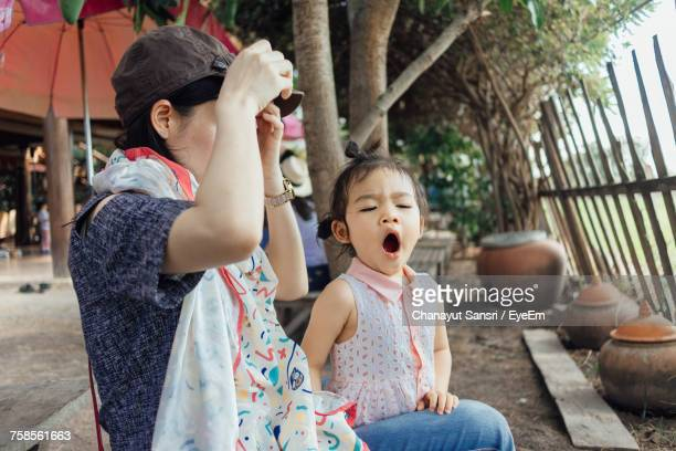 daughter yawning while sitting by mother - yawning mother child stock photos and pictures