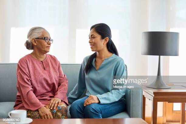 daughter-in-law and mother-in-law talking on sofa - mother in law stock pictures, royalty-free photos & images