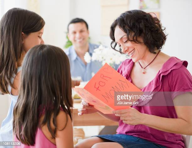 daughters giving mother mother's day card - mothers day card stock pictures, royalty-free photos & images